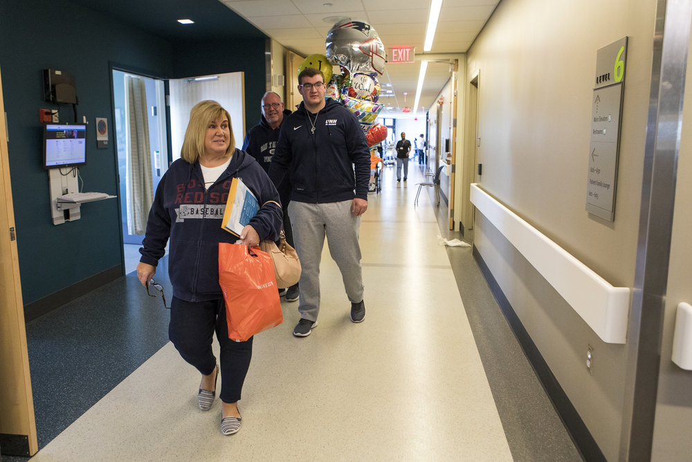 Connor Walker walks out of his hospital room with his parents Jean and Robbie after being released from Spaulding Rehabilitation Hospital on Oct. 25, 2018. When Connor was first brought to Spaulding, he was paralyzed and uncertain if he would be able to walk again. Now the college sophomore is able to walk, despite not having any feeling in his legs.