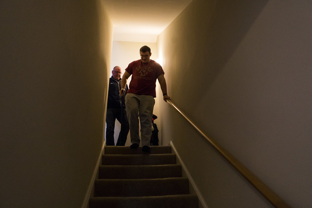 Connor Walker walks down the stairs with his father Robbie at their home in Marlborough on Oct. 31, 2018. One of the family's biggest fears upon Connor's return home was his ability to travel the three flights of stairs needed to take a shower.