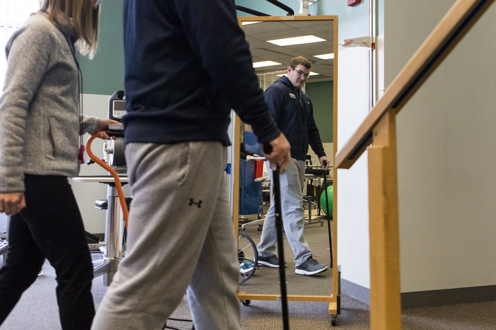 Connor Walker looks at his reflection while he practices walking during a physical therapist appointment at Spaulding Outpatient Center in Framingham on Oct. 31, 2018. Walker started using a cane to walk when his pain increased after being released from the hospital.