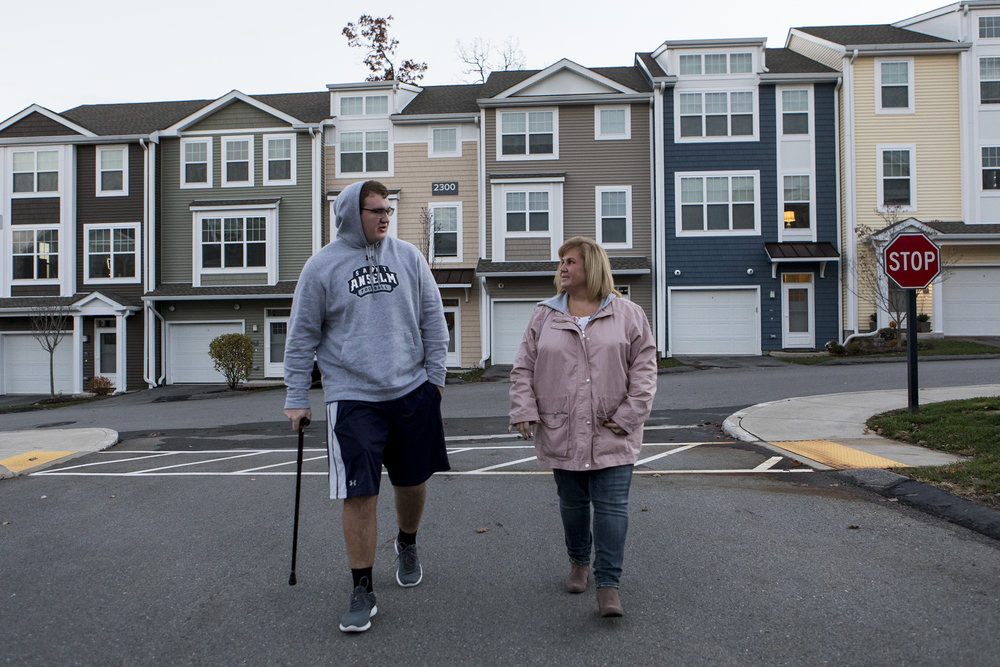 Connor and Jean walk to collect the mail outside of their family home in Marlborough on Nov. 7, 2018. Despite his back pain, Connor knows he must push himself to be physically active if he will be able to return to college in January.