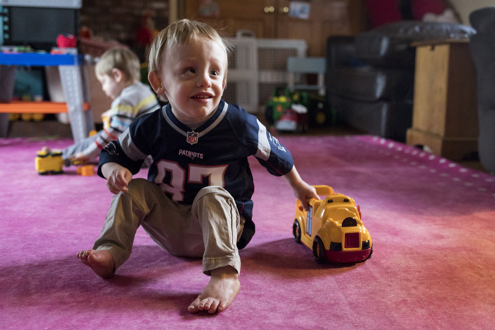 """Two-year-old Finn is nearly blind. He and his twin brother Mack were born premature at 24 weeks. Shortly after, his family learned Finn had an eye cancer and cerebral palsy. His conditions make it difficult for him to distinguish his toys in the bright light or see the distance between the dark chairs and hardwood floor. With funds from an Advocates grant, his family was able to purchase a brightly colored rug to help make sense of his environment. """"For strangers to award us this meant so much to us,"""" His mother Shannon said. """"It's hard when you want to give them everything you can and sometimes you can't."""""""
