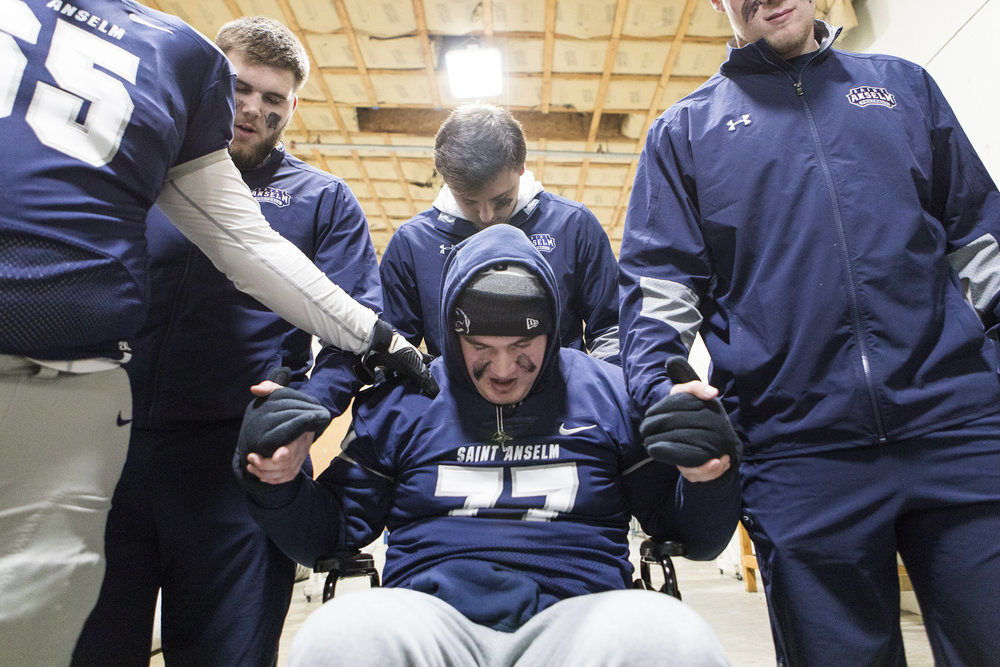 Connor Walker prays with his teammates before their final football game of the season at Saint Anselm College in Manchester, New Hampshire, on Nov. 10, 2018. After sustaining a spinal cord injury from a helmet-to-helmet collision in September, Walker will no longer be able to play football.