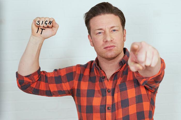 """Jamie Olivercom a palavra """"assine"""" escrita na mão. / Foto: Divulgação Food Revolution Day"""