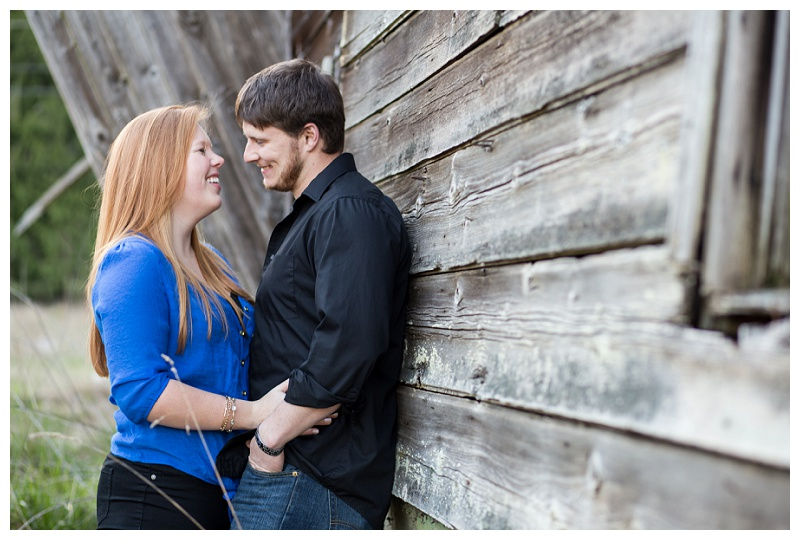 Couple leaning against barn