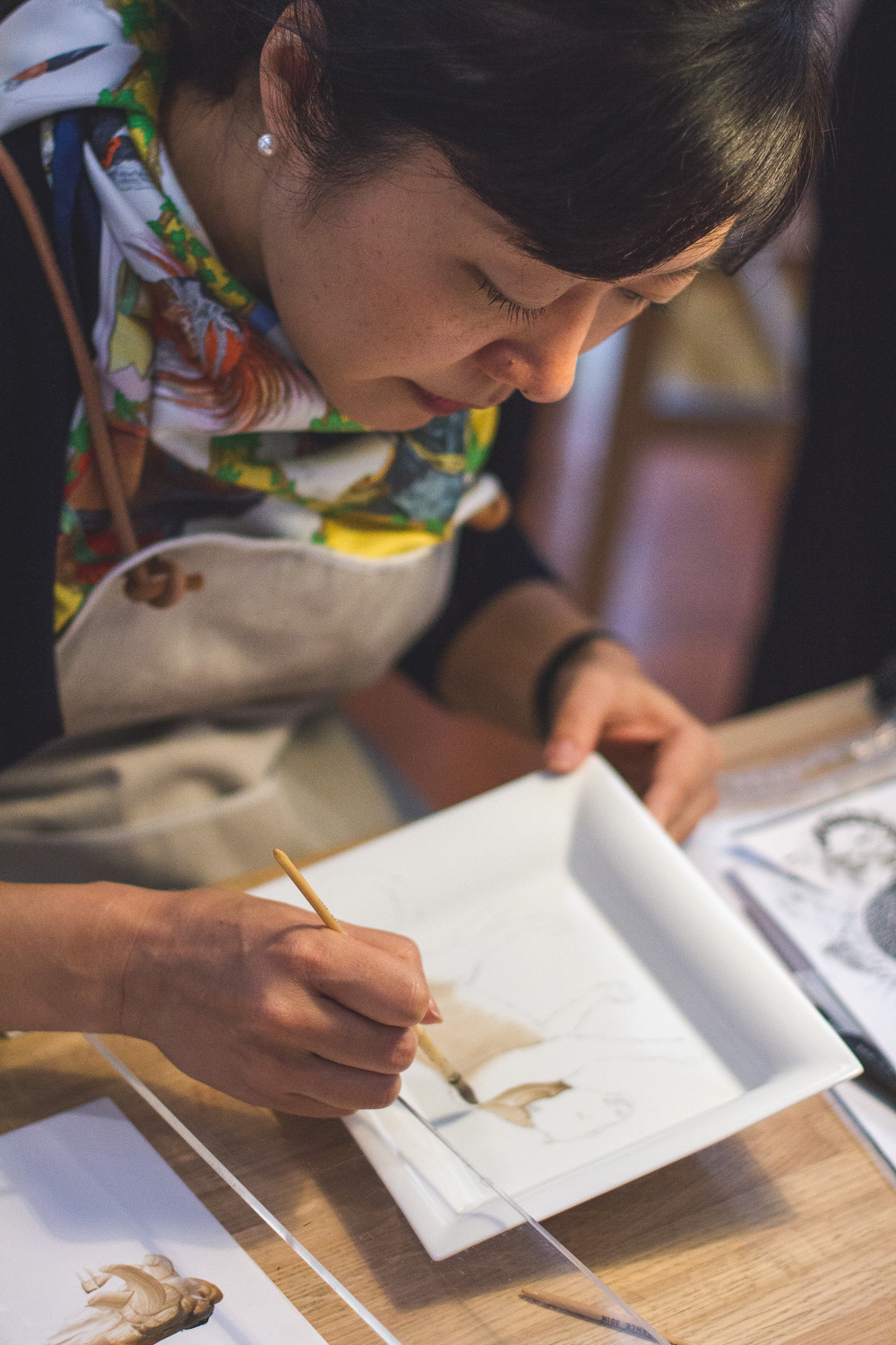 An artist paints a design onto a Hermès plate Photo: Helena McMurdo