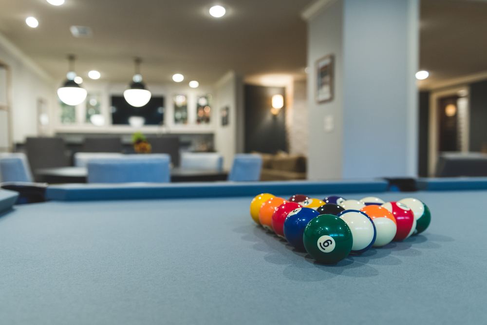 The grey slate pool table made the game work with the decor.   www.saranobledesigns.com