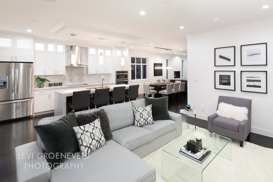 The family room off of the kitchen is a more relaxed place to watch TV and hang out. A cozy area rug and a sectional sofa make it a comfortable place to lounge with plenty of room for a group. Four black and white prints of Vancouver by  Levi Groeneveld  add character to the space.