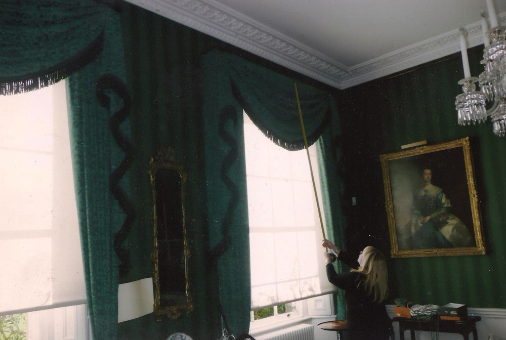 London- Teal green curtains with single swag and tail design with heavy bullion fringe trimming.