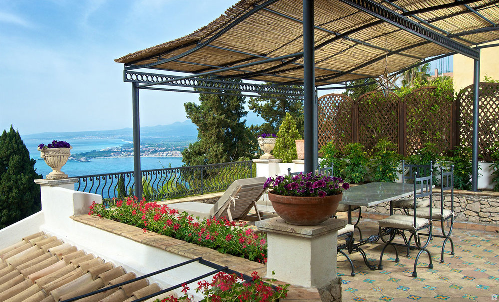 Villa Carlotta's terrace view. The hotel has a lush garden and a refreshing swimming pool terraced above the rose-coloured tiles of an ancient chapel.