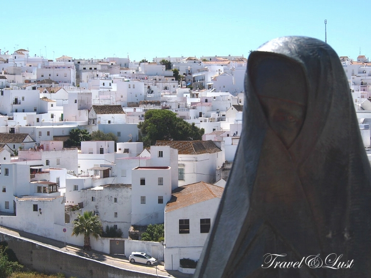 Statue of traditional dress (estatua de Las Cobijadas) with views of the newer part of town.