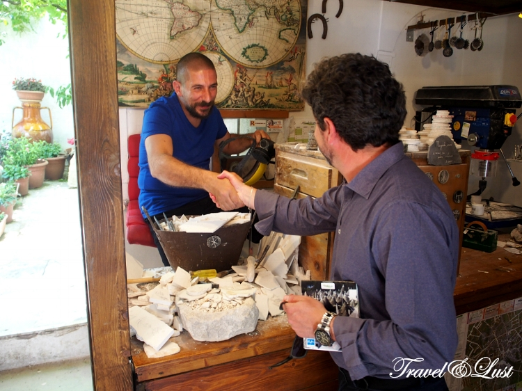 Augusto from Ad Pugliam shaking hands with a local shop worker.