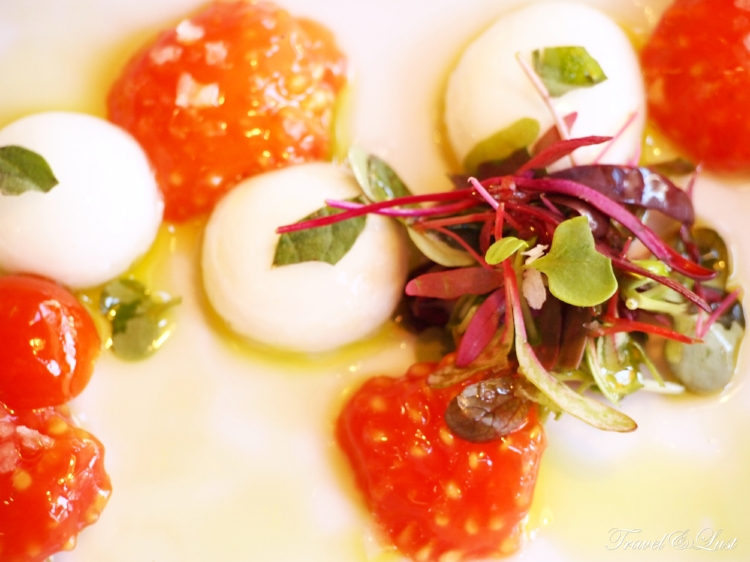 Fresh mozzarella spheres with tomato hearts and aromatic herbs.
