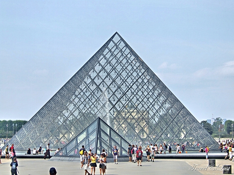 The Louvre pyramid during the day. Over 380,000 objects and and 35,000 works of art are displayed here.