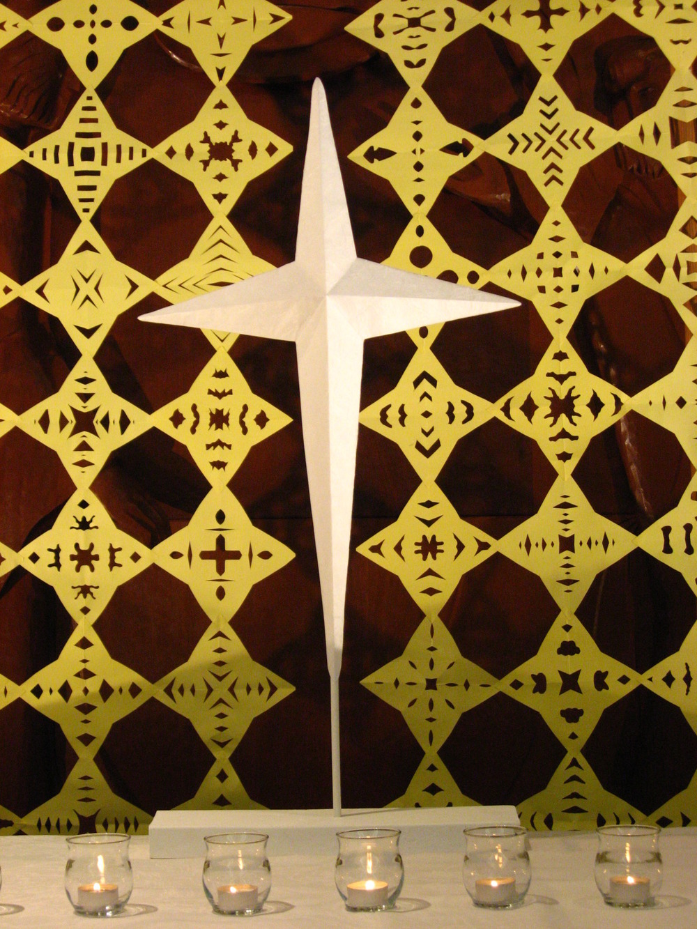 Altar detail, cut paper star-cross shapes, Epiphany
