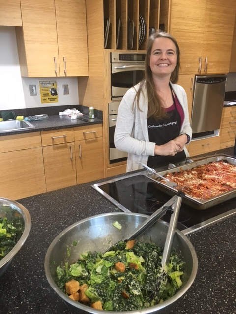 Casey McCurry, Columbia's Cooking Program Coordinator, happily serving a veggie lasagna with a cashew basil cheese and vegan cesar salad with our home-made and oil-free croutons.