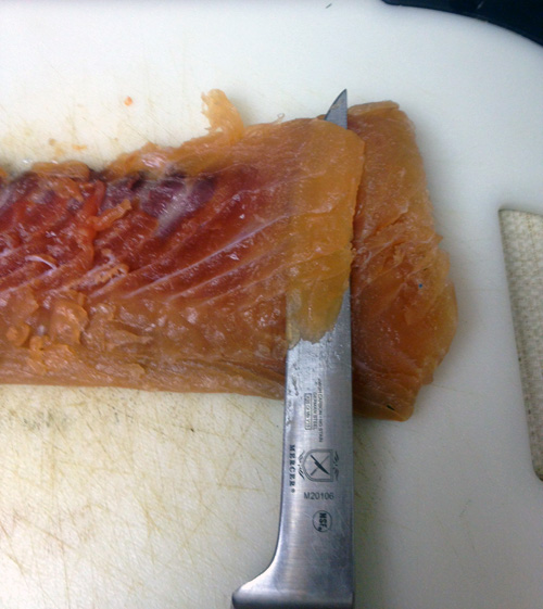 Slice the lox very thinly, at an angle so extreme your knife is almost flat on the fish.