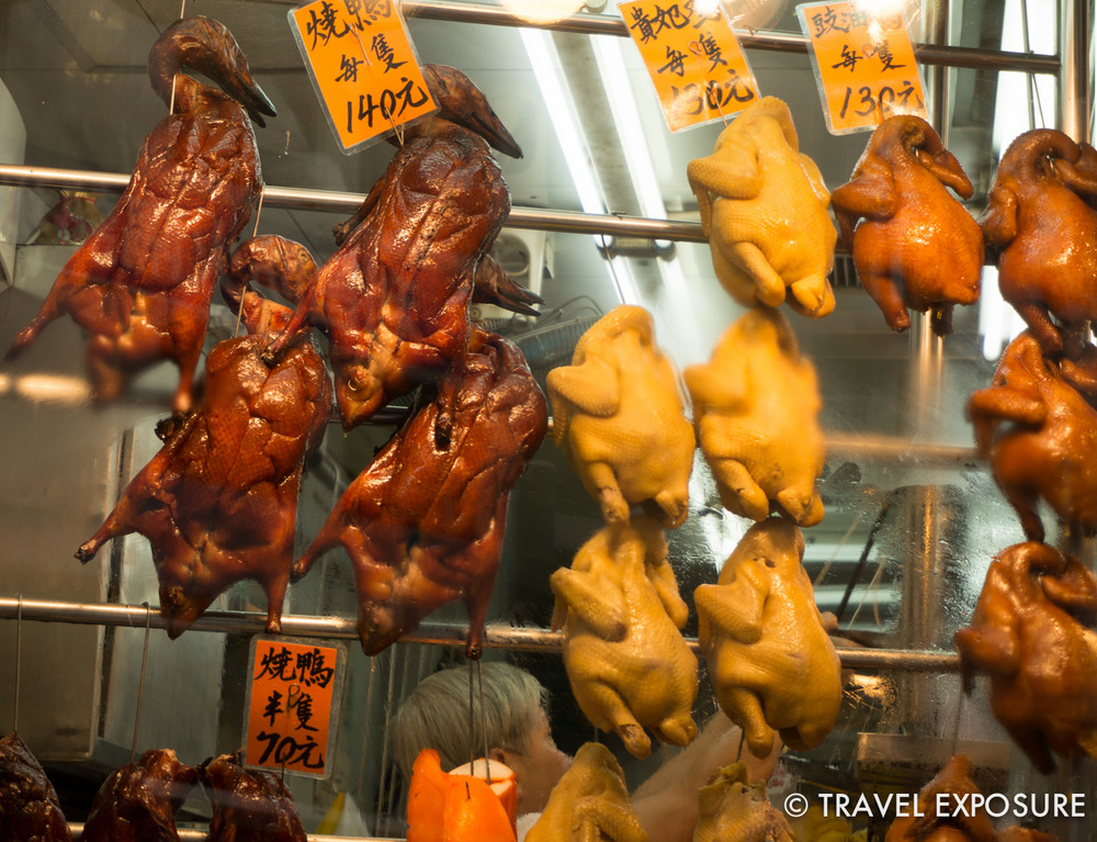 Peking ducks and poultry hanging in a shop window.