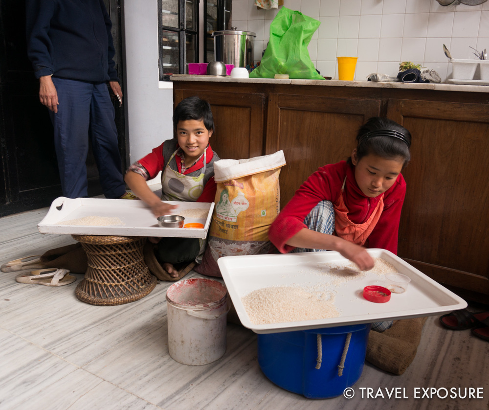 Pemla is taking care of these two girls from less fortunate families. Here they are in the kitchen cleaning some rice.