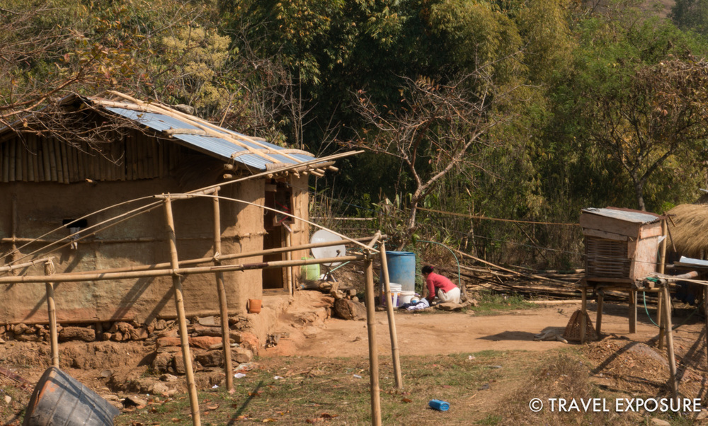 A woman washing clothes outside next to her satellite dish inMartam Village in Sikkim