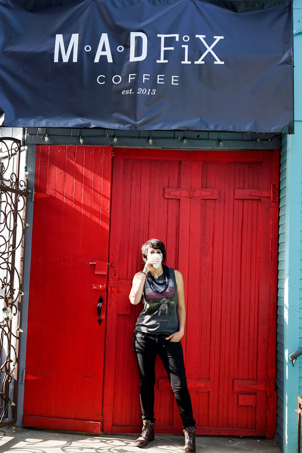 Dottie enjoys a cup of coffee in front of the welcoming red portals at M.A.D. FiX. Photo by Jose Lopez.