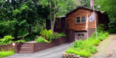 A secluded log home with lush gardens and berry patches.