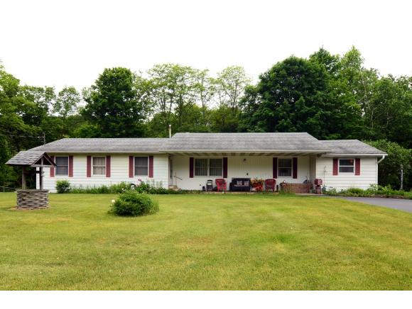 A large Ranch home on over an acre with rolling lawns and a lovely back deck.
