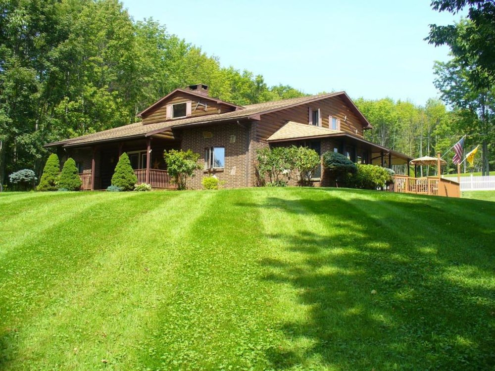 Country contemporary on almost 8 acres with an outbuilding and large pond.