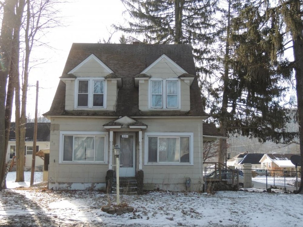 A 2-story home on a corner lot with 4 bedrooms, including a walk-up attic.