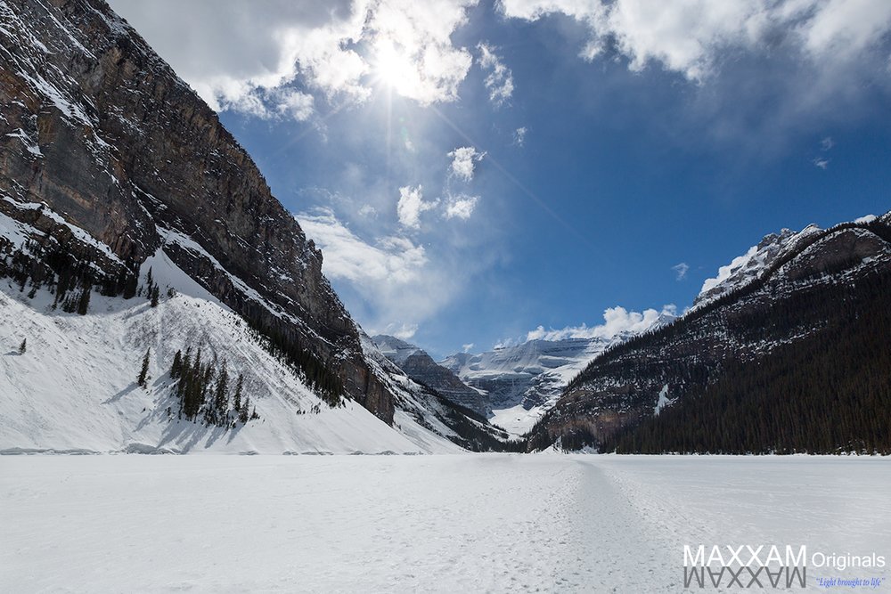 Lake Louise in the early weeks of spring is still frozen over, allowing visitors to walk across what would normally be open water.
