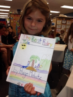 First grade student displaying her book during Author's Tea.