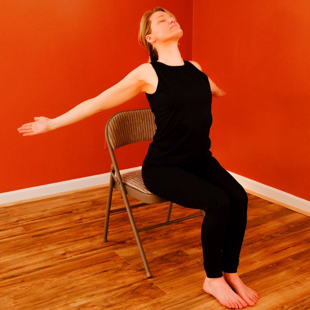 Begin by sitting tall on Chair with your back straight.    Inhale and open your arms out to the sides squeezing your shoulder blades together, arching your back and gently looking up