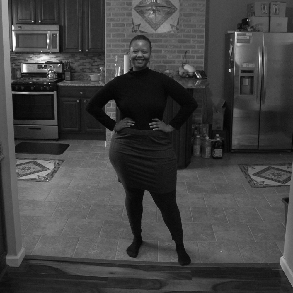 Image of a black and white photo. A tall, Black woman dressed in all black and grey. She is standing center in the middle of her kitchen with her hands on her large hips.. She is smiling and looking straight into the camera.