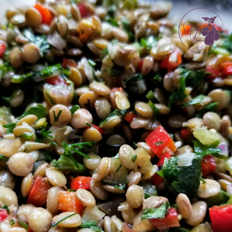 Image of zoomed in summer-y lentil salad with vibrant vegetables, herbs, and green lentils.