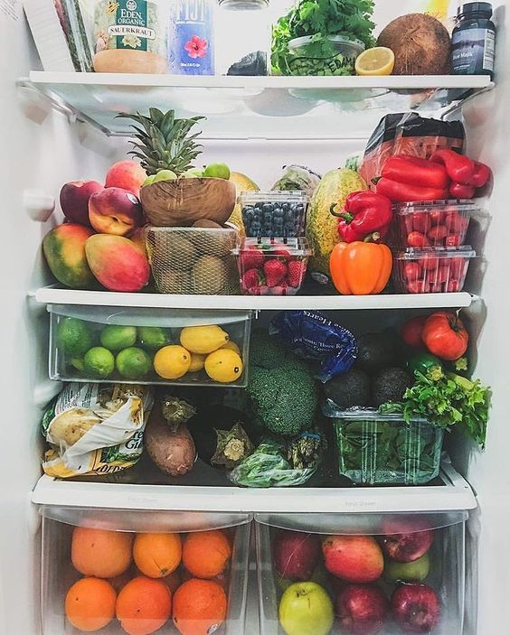 Source: @tropicallylina  Image of a open refrigerator overflowing with fresh, colorful produce from top to bottom.