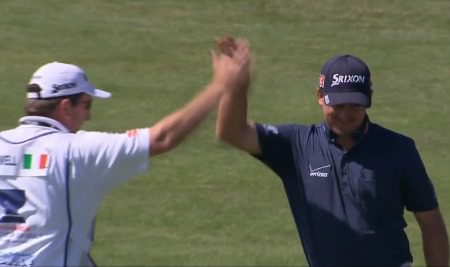 Graeme McDowell high-fives his caddie after holing out from the fairway for his eagle at the ninth but Ireland are 10 shots behind in the World Cup of Golf at Royal Melbourne.