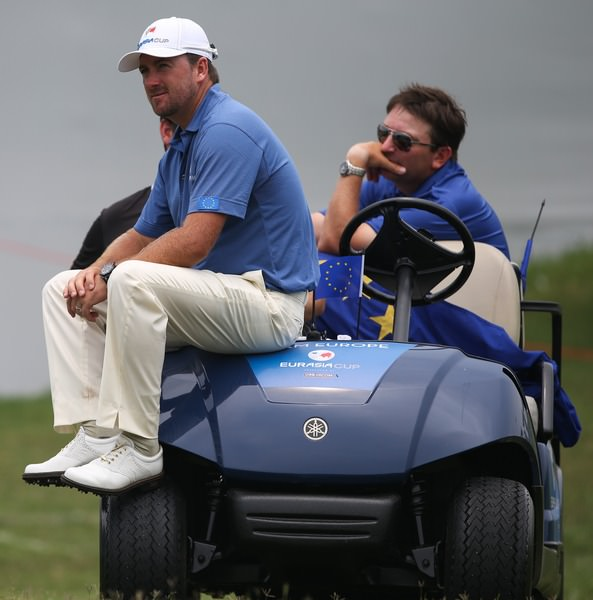 Team Europe's Graeme McDowell and caddie Ken Comboy watch the matches unfold after they were defeated 3&2 by Team Asia Captain, Thongchai Jaidee during the final day singles. Picture: David Lloyd /  www.golffile.ie