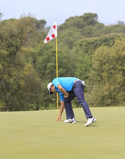 Gareth Maybin retrieves his ball from the hole on the eighth. Picture: Thos Caffrey /  www.golffile.ie