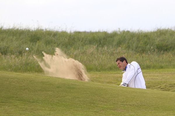 Colm Campbell blasts out of a greenside trap at the 18th. Picture: Thos Caffrey /  www.golffile.ie