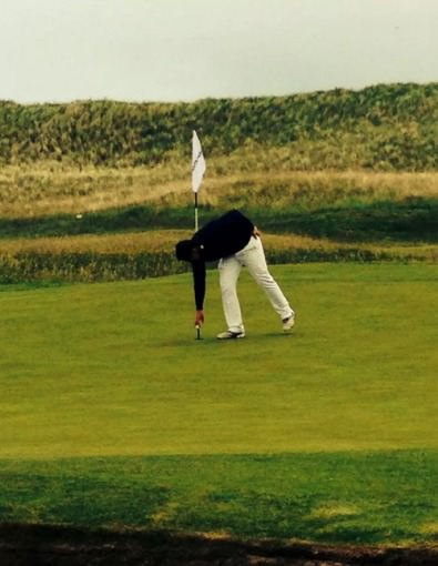 Colm Campbell retrieves the ball from the hole following his hole in one at the 15th. Picture via Twitter.