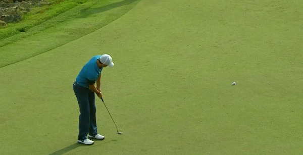 Rory McIlroy's birdie putt topples in at the 18th
