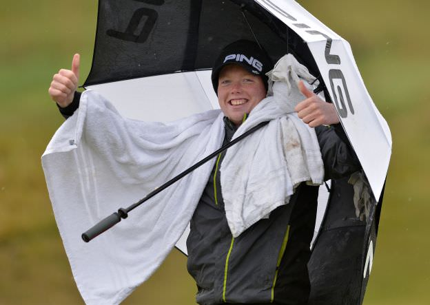 Keeping dry......Robin Dawson (Faitlegg) smiling despite the weather on the 13th fairway in the second round of the 2015 Irish Amateur Open Championship at The Royal Dublin Golf Club. Picture by  Pat Cashman