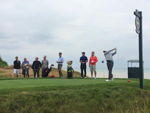 Rory McIlroy, watched by that group that includes his father Gerry, his coach Michael Bannon, his assistant Sean O'Flaherty, his best friend Harry Diamond and his caddie JP Fitzgerald at Whistling Straits today.
