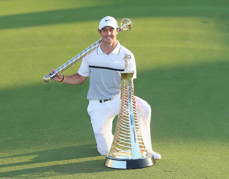 2015 race to dubai winner Rory McIlroy poses with the harry vardon and dp world tour championship dubai trophies