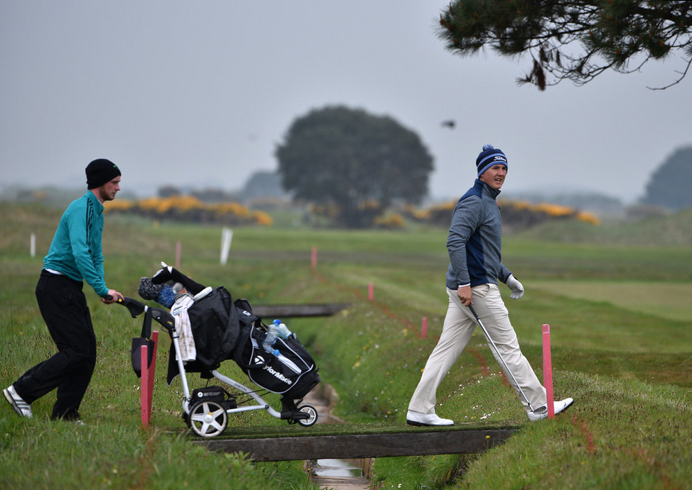Follow the leader. Colm Campbell (Warrenpoint) walking across the bridge at the 13th hole followed by his caddy Stephen Coulter in the third round of the 2016 Flogas Irish Amateur Open Championship at The Royal Dublin Golf Club. Picture by  Pat Cashman