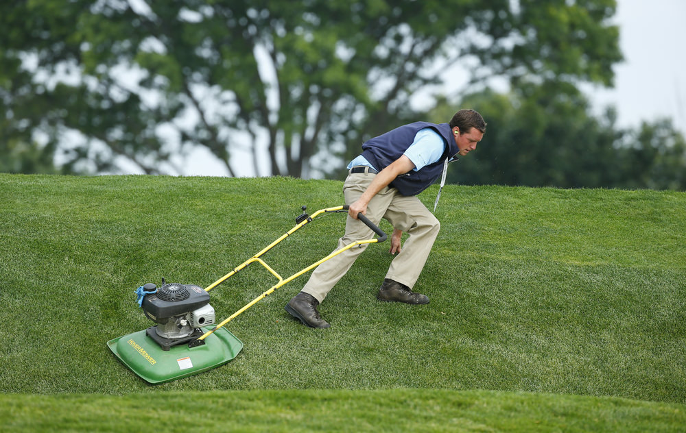 A grounds crew member mows grass during a practice round for the 2016 U.S. Open at Oakmont Country Club in Oakmont, Pa. on Wednesday, June 15, 2016. (Copyright USGA/Jeff Haynes)
