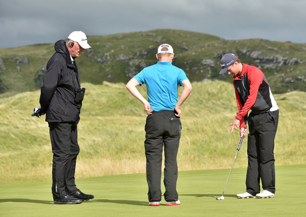 Peter Kerr (Royal Portrush) explaining a ball movement to referee Dermot Logue and Geoff Lenehan (Portmarnock) on the 9th green during his quarter final match at the AIG Irish Amateur Close Championship at Ballyliffin Golf Club. There was no penalty as the wind, not the player, caused the ball to move. Picture by  Pat Cashman