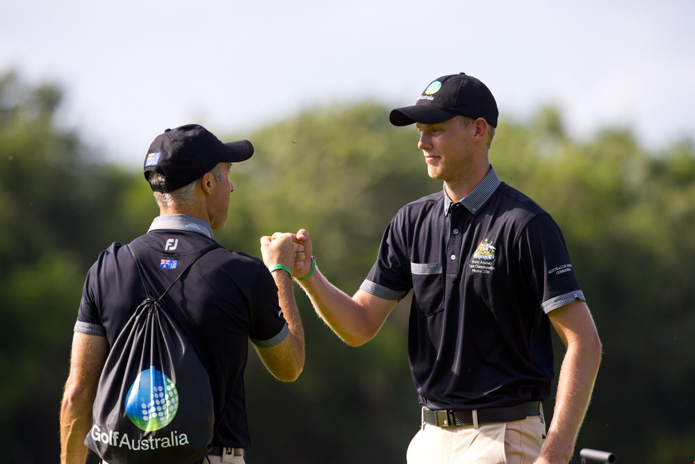 Australian captain Matt Cutler, (left), knuckles Cameron Davis of Australia, after Davis sinks his birdie putt at the par 5 seventh hole, during the second round of the 2016 Eisenhower Trophy at El Camaleon G.C. in Riviera Maya, on Thursday, Sept. 22, 2016. (Copyright USGA/Steven Gibbons)