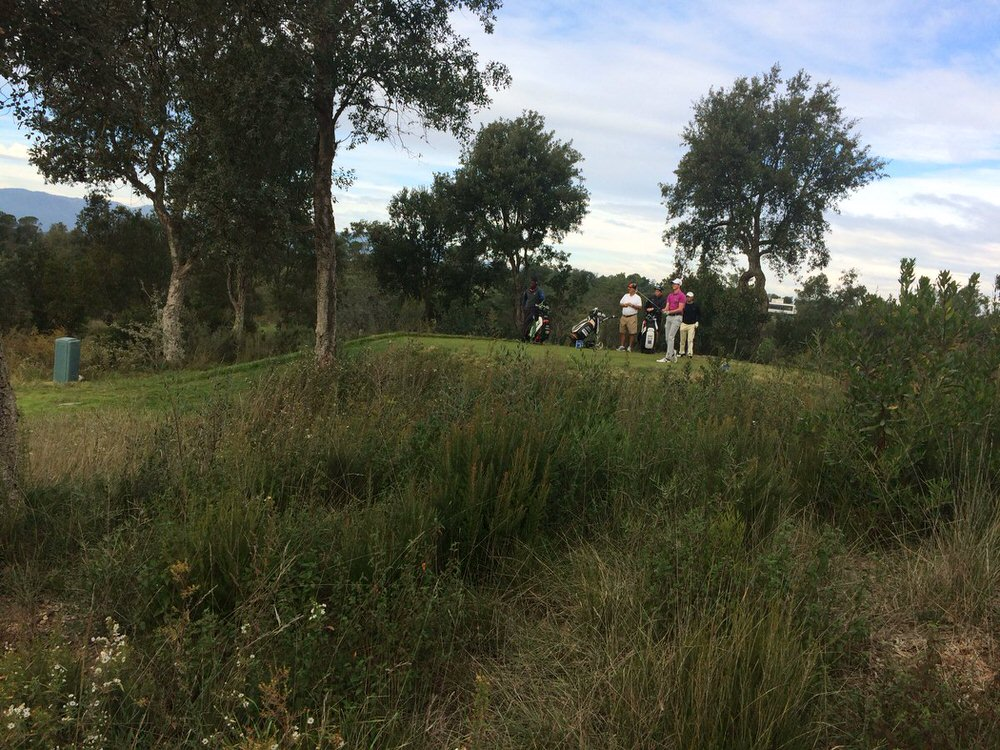 Gary Hurley watches his tee shot down the par-five third at PGA Catalunya Resort as his South African caddie Joseph looks on