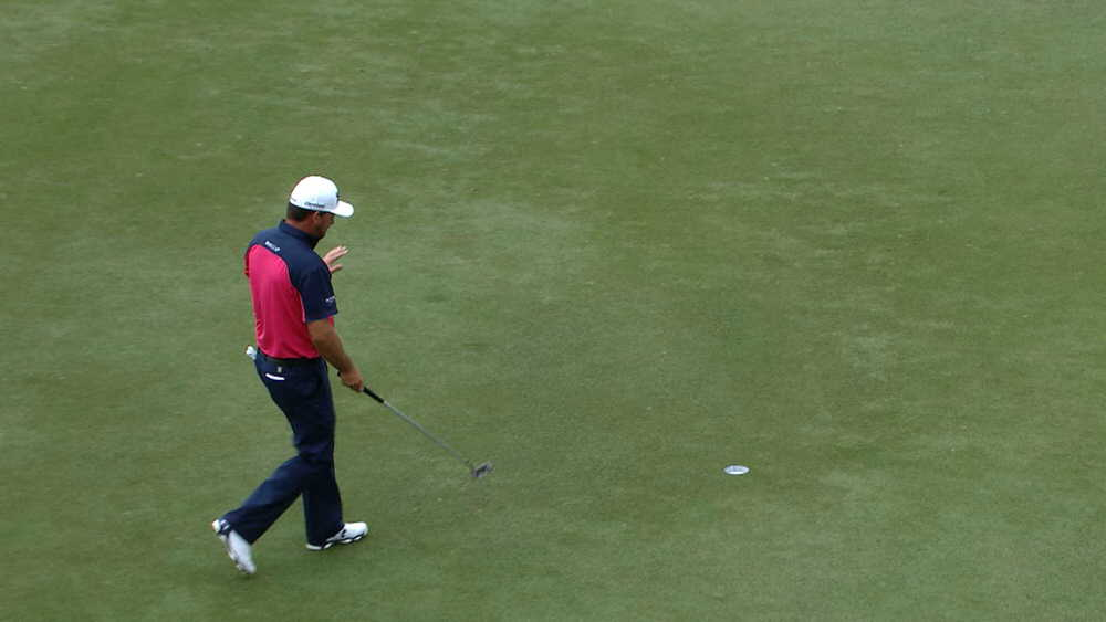 Graeme McDowell goes to pick his ball out of the hole after a birdie