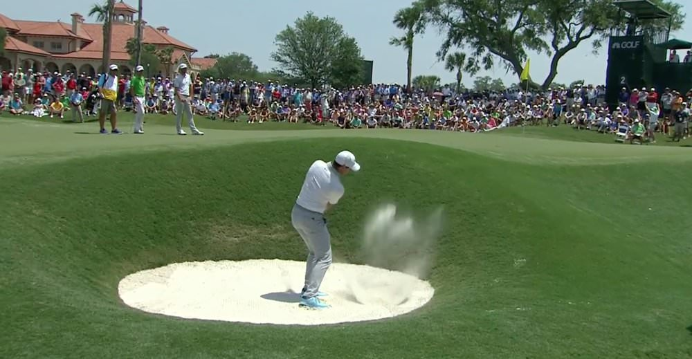 Rory McIlroy plays a bunker shot at the par-five second